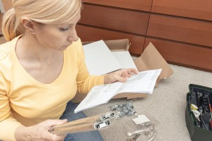 Woman assembling DIY furniture following instruction book