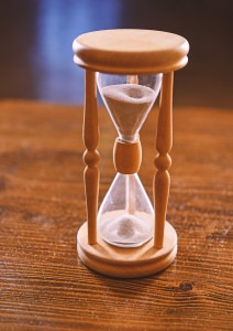 Old-fashioned hourglass on wooden table